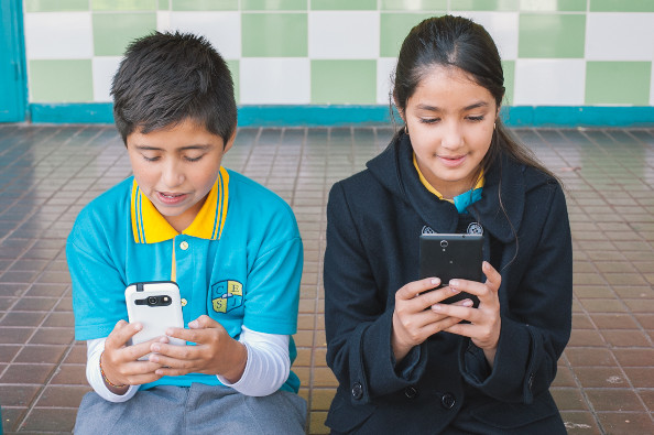 Niño y niña de uniforme escolar usando sus smartphones. Lucen alegres y concentrados. Están sentados en el suelo... pareciera que el suelo tiene un escalón que baja hacia un patio.