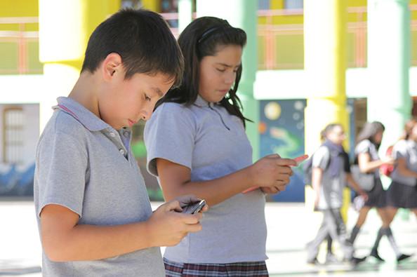 un y una estudiante revisan sus dispositivos móviles en el patio de su escuela